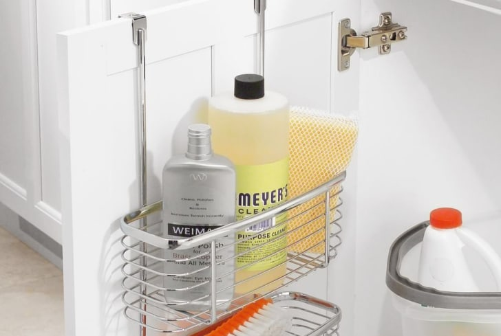 A metal storage caddy with cleaning products inside hangs from the top of a white cabinet door.