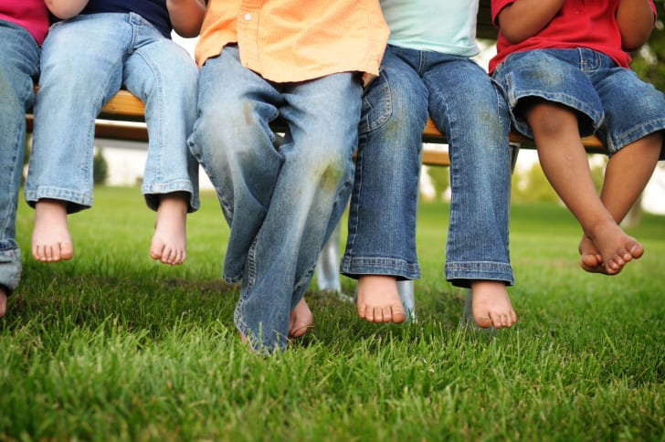 Four people sitting on a bench with the photo cropped from the waist down. All of their denim-clad knees are covered in grass stains.