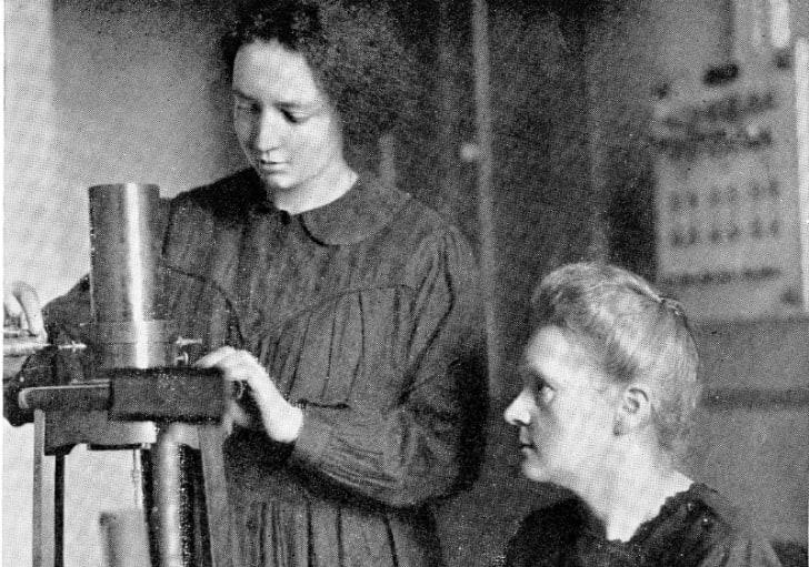 A black and white photo of Irene and Marie Curie in the laboratory in 1925.