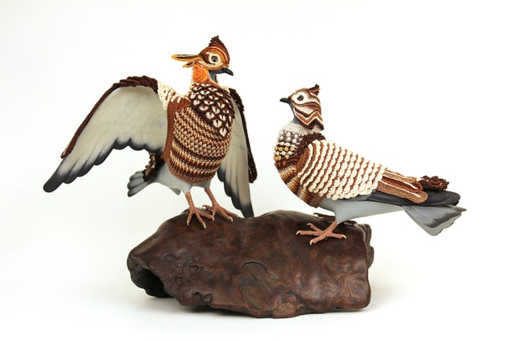 Two birds in crocheted costumes depicting heath hens appear to interact on top of a rock.