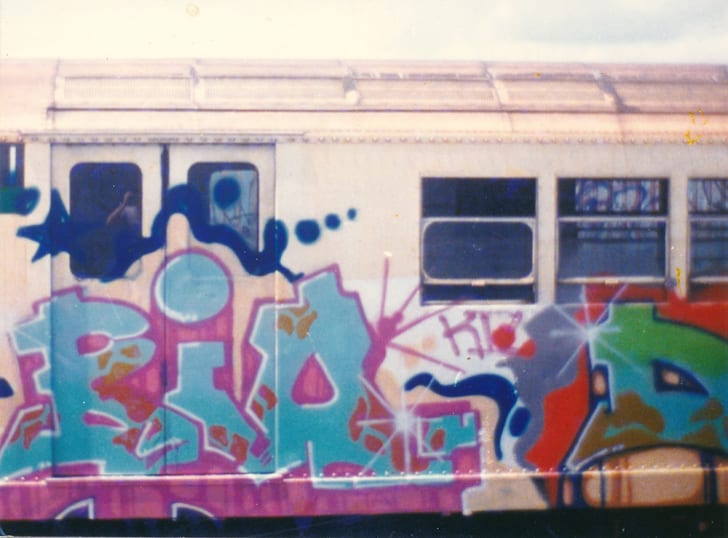 "Pink and blue lettering reads ""Bio"" on the outside of a subway car."