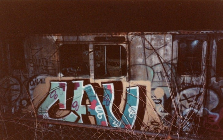 "A photo taken at night shows a subway train tagged ""Cav."""