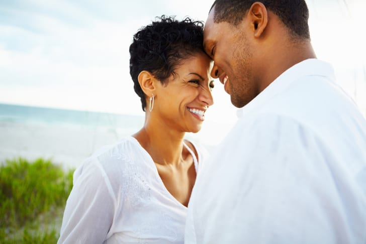 A black man and woman, with their foreheads touching, smiling