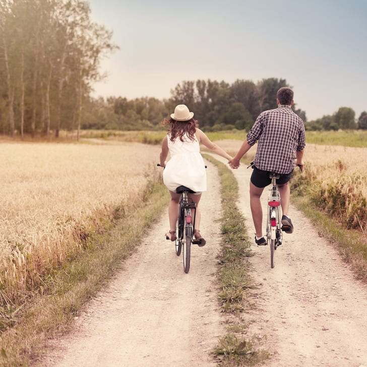 A man and a woman, each on a bicycle on a rural road, holding hands