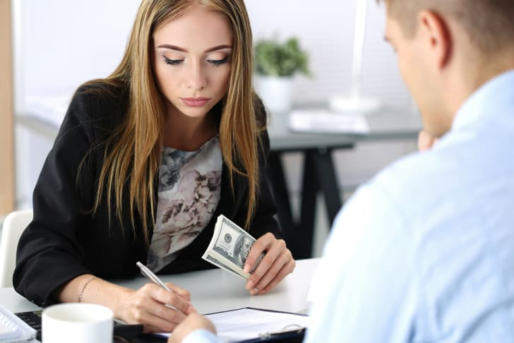 A young businesswoman holding money and writing on papers