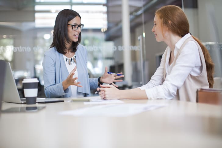 A young business woman counseling another young woman