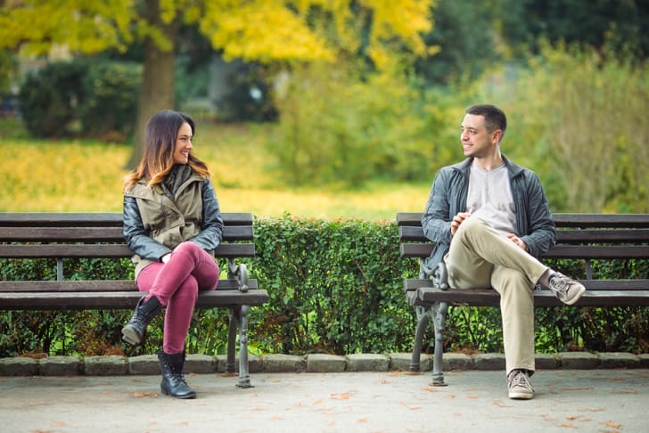 A young man and a woman sitting on park benches near each other