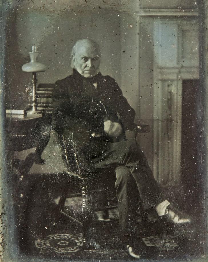 John Quincy Adams sits in a portrait studio in 1843.