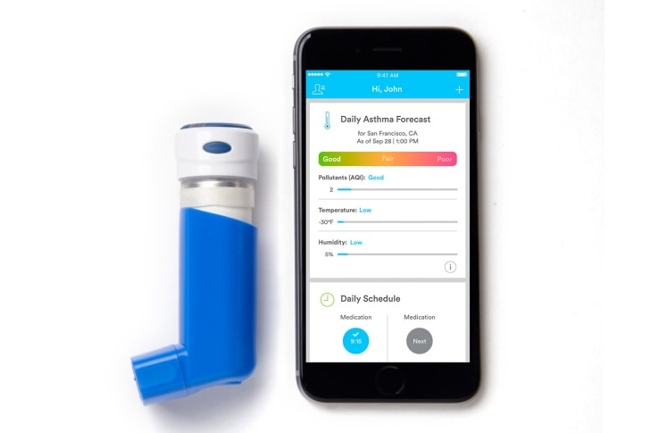 An inhaler with a sensor on top of it lies next to a smartphone open to the Propeller app.