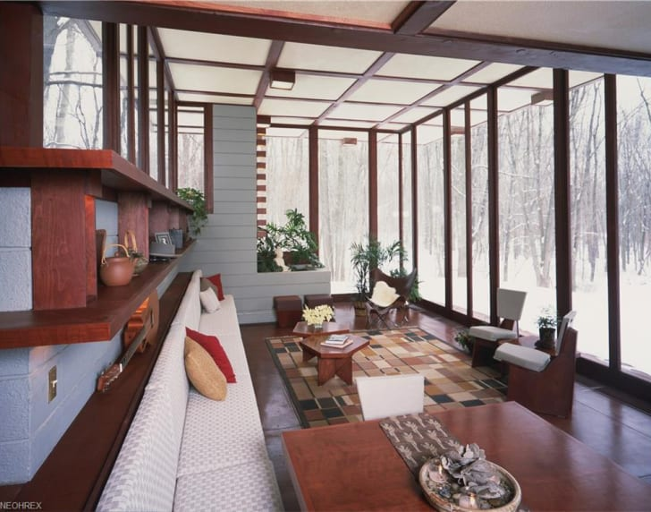 A retro-looking living room features floor-to-ceiling windows.