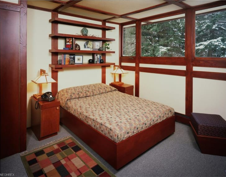 A bedroom is filled with vintage wooden furniture.