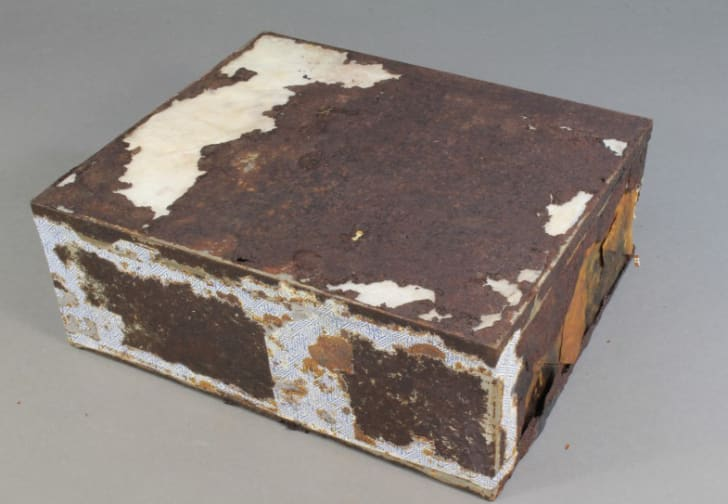 A rusted rectangular tin holds a century-old fruitcake.