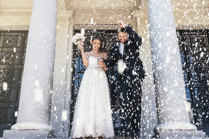 Wedding guests throw rice at a newly married couple
