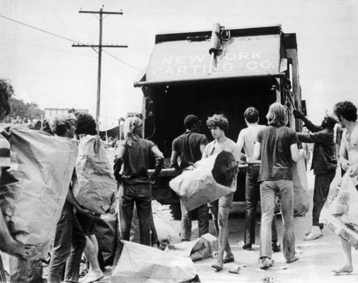 People clean up the garbage left behind at Woodstock in 1969