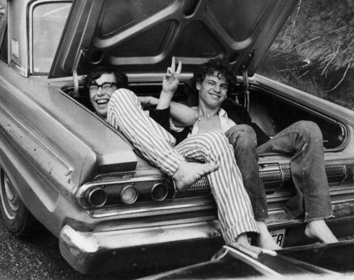 Attendees at Woodstock pose while sitting inside a car trunk
