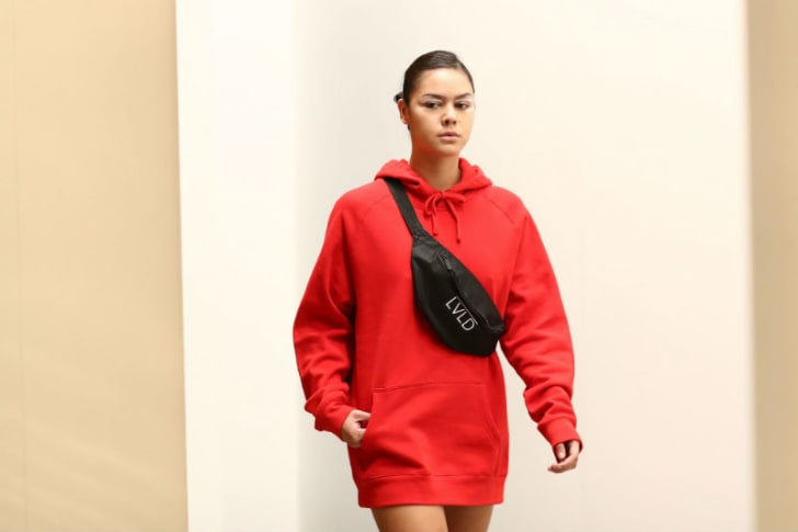 A model sports a fanny pack, also known as a belt bag, across her shoulder