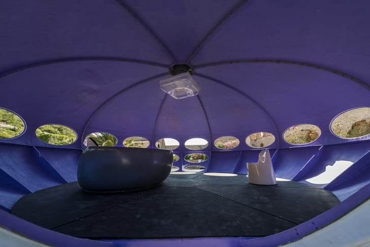 The rounded interior of a Futuro home with two experimental retro chairs inside.