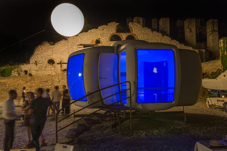 A Maison Bulle à Six Coques home lights up with a blue glow at night in the sculpture park.