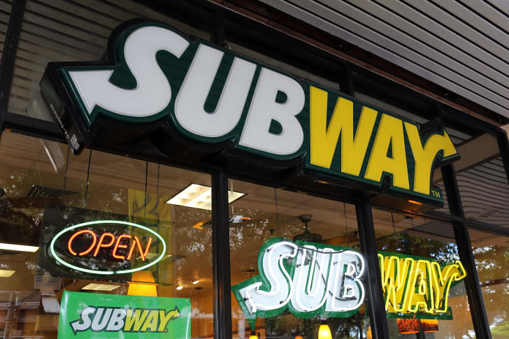The window of a Subway sandwich chain store with neon signs and advertisements in the window.