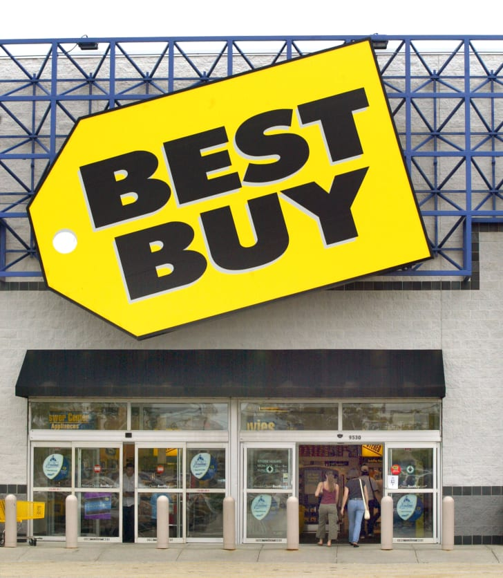 "The outside of a Best Buy retail store with a large yellow tag ""Best Buy"" logo over the entrance."