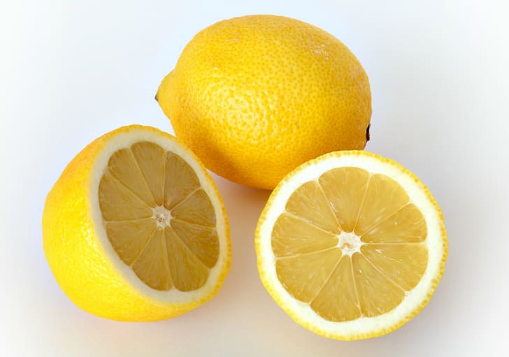 Photo of two lemons, one sliced in half.
