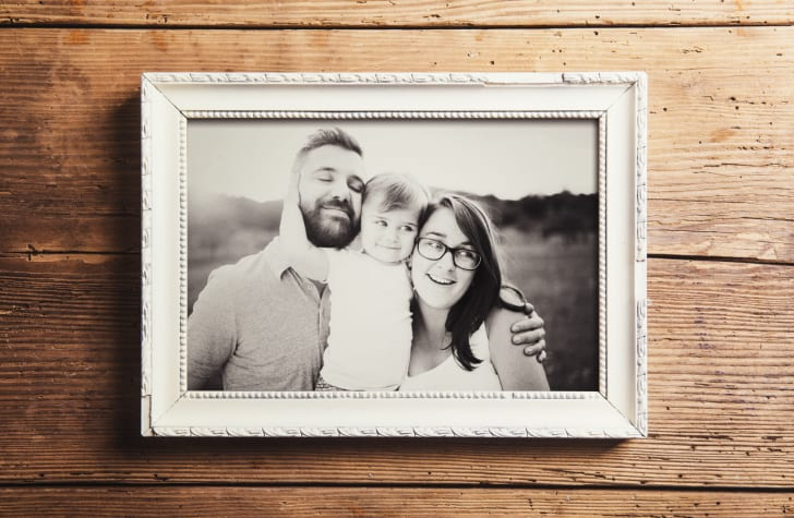 A black-and-white portrait of a family inside a white antique picture frame.