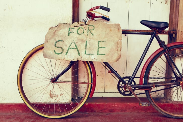 "A red bicycle on a porch with a ""For Sale"" sign tacked to its side."