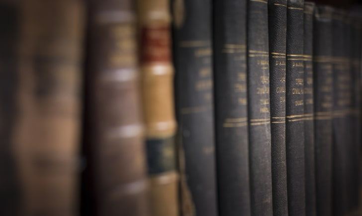 Old, dusty hardcover books on a shelf
