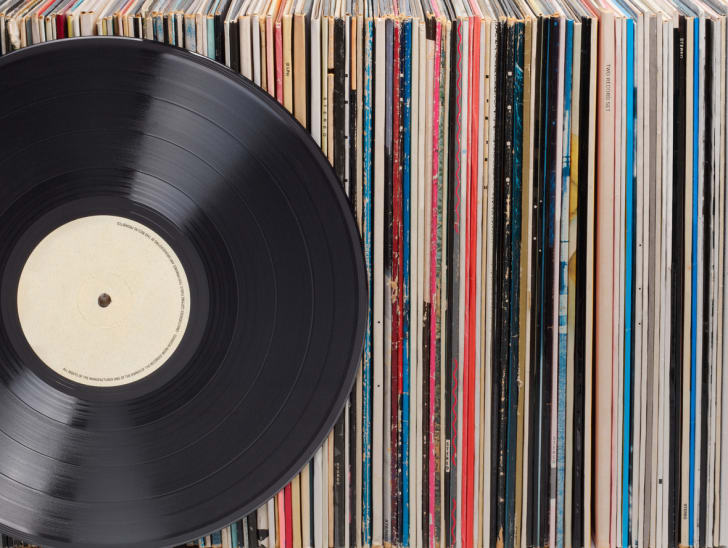 A stack of vinyl records sitting in a row