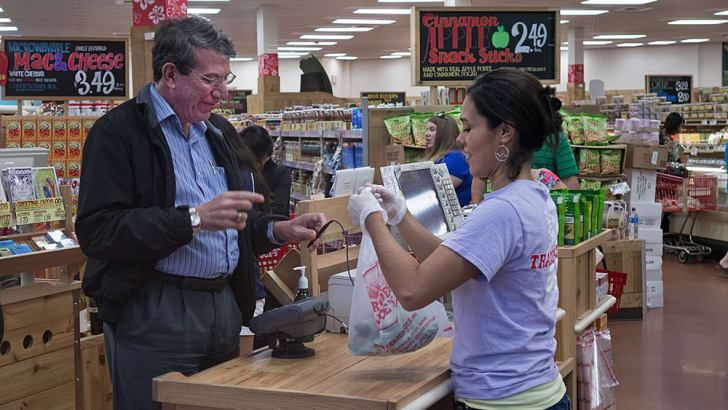 A clerk bags groceries at Trader Joe's