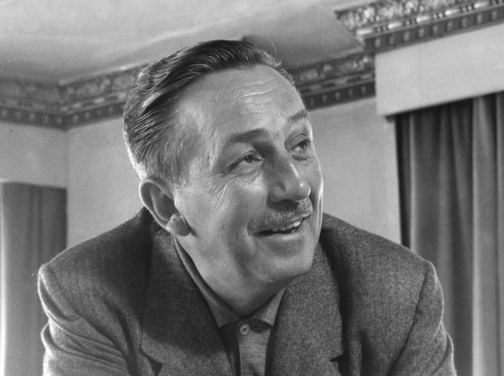 A black and white photo of Walt Disney wearing a suit coat and smiling up and to the right.