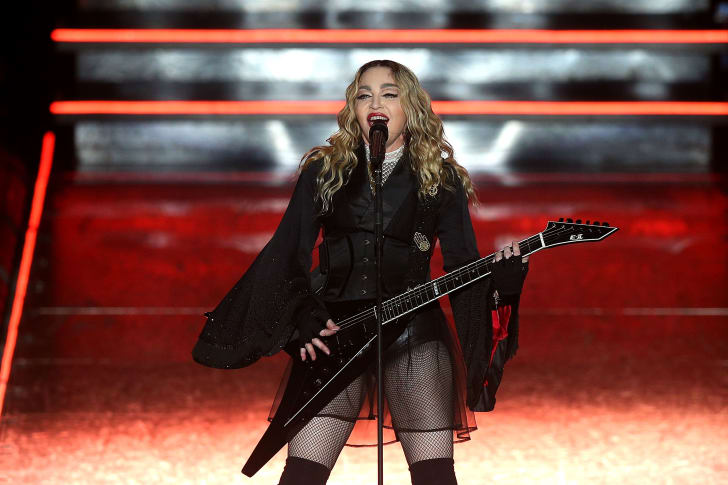 The singer Madonna singing into a microphone on stage, wearing a black drapey costume and holding a black guitar.
