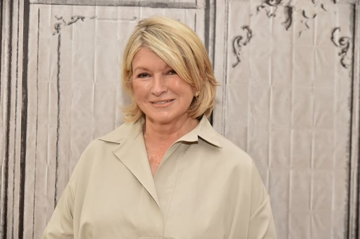 Martha Stewart, wearing a tan collared shirt, stands in front of a textured background and smiles at the camera.