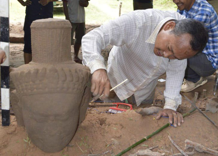 An archaeologist dusts off the head from a 12th-century Cambodian statue.