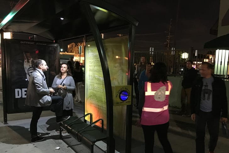 """People gather at night under the bus stop awning. The """"try street perfume"""" box glows blue."""