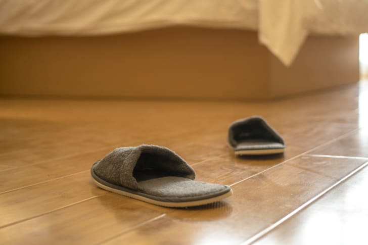 Slippers next to a bed.