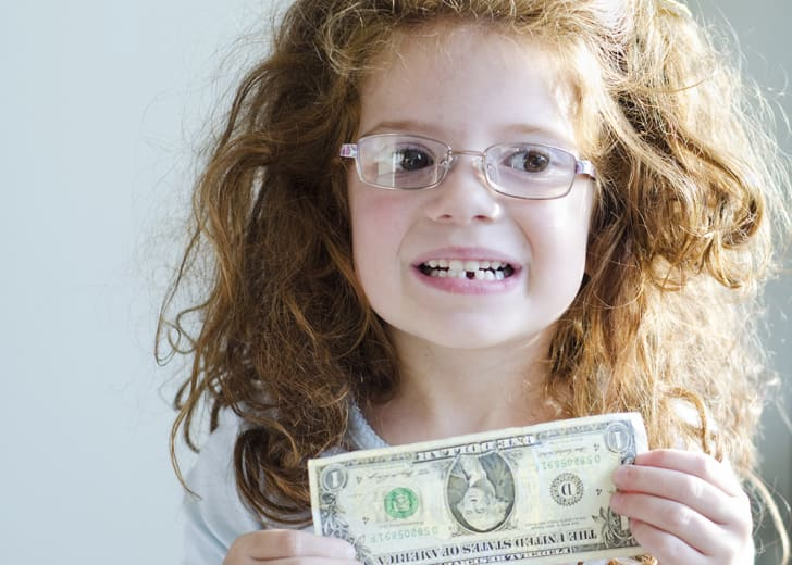 A little girl with money she received for losing a tooth.