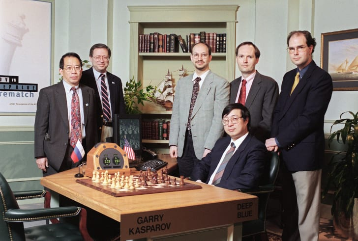 Six men pose with a chess board and timer. On one side of the board, a sign reads Garry Kasparov. On the other side, a computer keyboard and monitor represent Deep Blue.