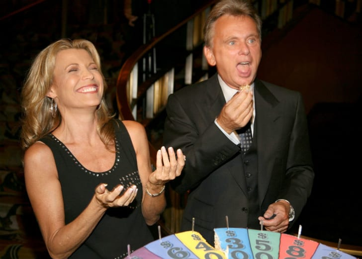 Pat Sajak stands next to co-host Vanna White