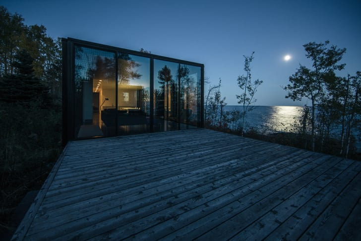 A cabin with floor-to-ceiling windows looks out over a moonlit lake.