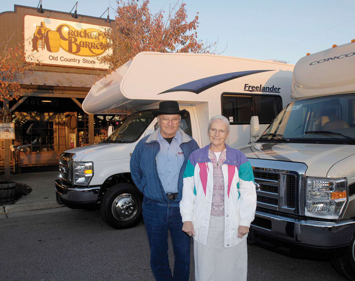 Ray and Wilma Yoder stand in front of two RVs outside a Cracker Barrel.