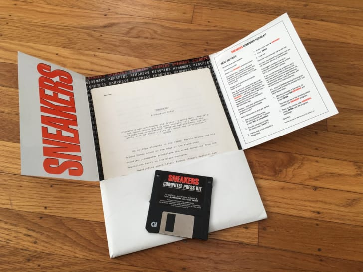 A paper folder lies open on a wooden floor, with a black floppy disk on top. The folder is labeled SNEAKERS in giant red letters, as is the floppy. Inside the folder is printed material. On the right flap of the folder are instructions on how to load it.