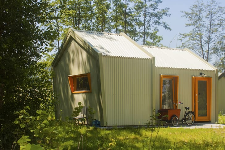 A bicycle is parked outside a slanted green tiny house.