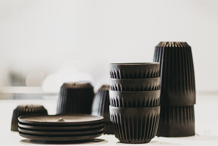 A stack of black cups and saucers of various sizes on an espresso machine.