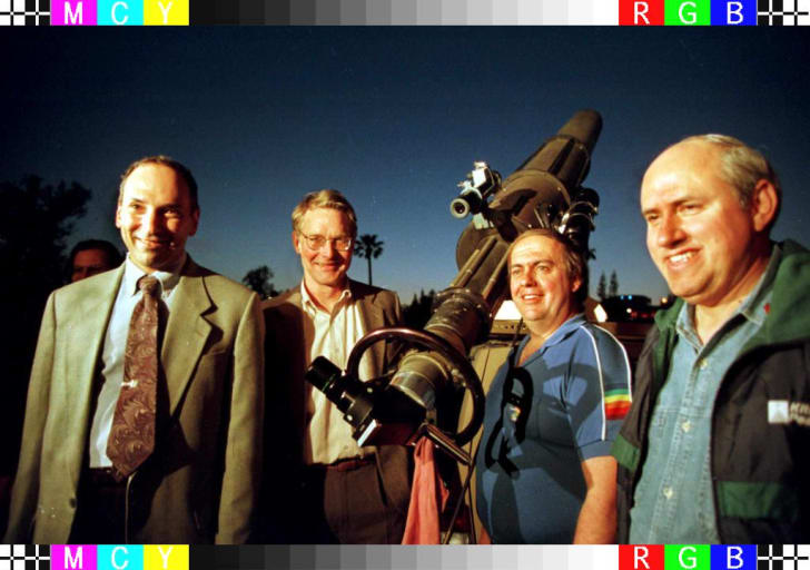 Four men smile, posing outdoors next to a large telescope at night.