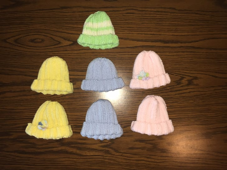 Seven pastel knit caps lie on a wooden table.