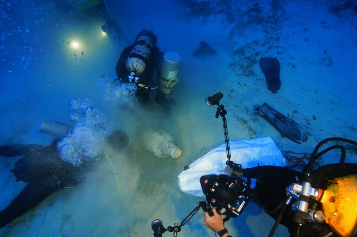 Divers inspect and survey an ancient amphora near the shipwreck site.