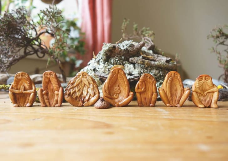 Wooden carvings of men on a table.