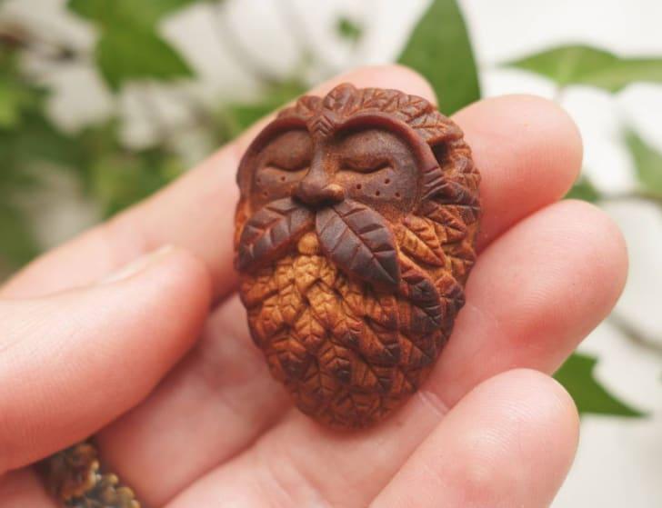 Hand holding a wooden talisman.