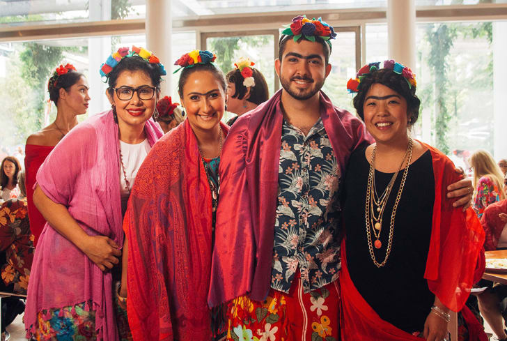 Three women and one man dressed up as Frida pose for a picture.